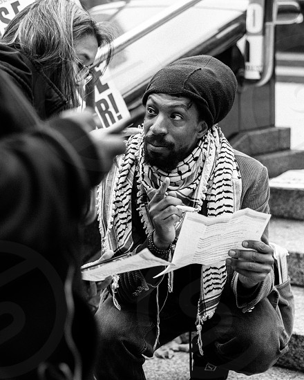 A man going over notes with a colleague at a rally in NYC. photo