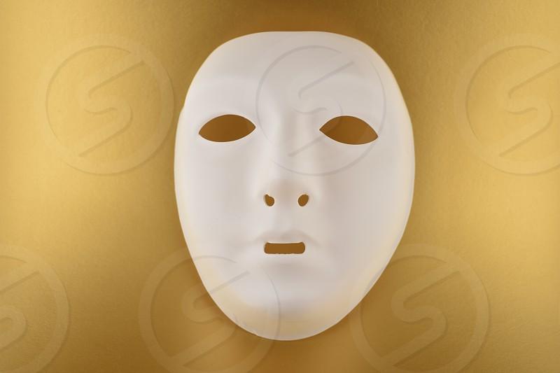 Plastic white face mask. White mask on a gold background. Plastic human mask photo