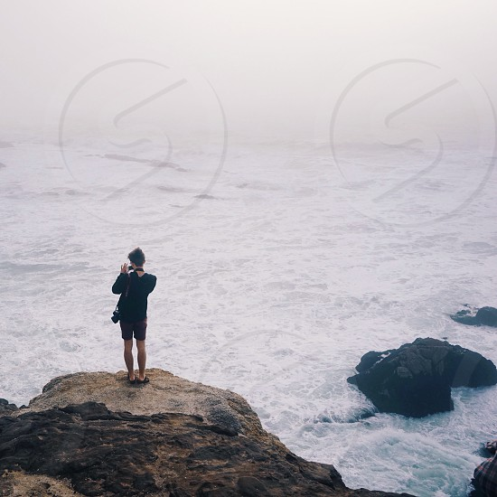 person standing on a rock near the ocean photo