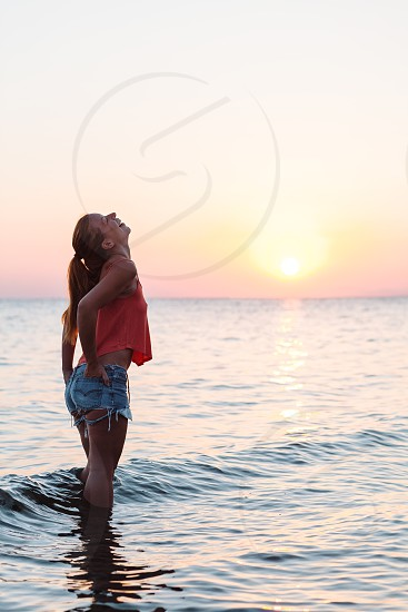 Young woman enjoying sea and sunset photo