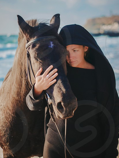 Young Blonde woman stroking and hugging horse. Beautiful lady with her black stallion on seashore enjoying nature. Love and friendship concept. Waves ocean background photo