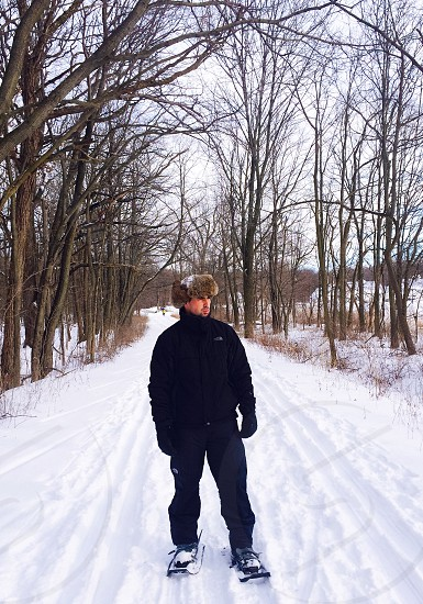 man in winter coat and fur hat on skis in middle of path between winter trees photo