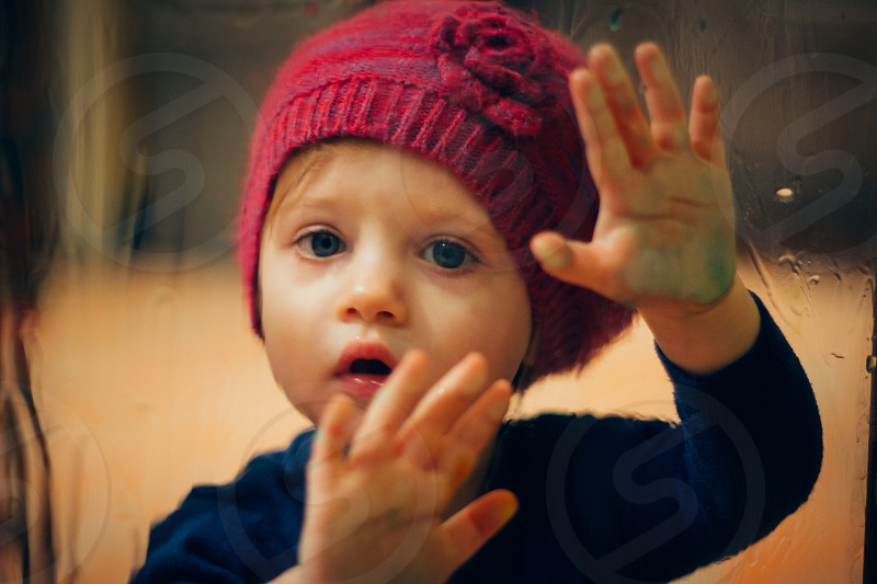 baby in blue sweatshirt and red knitted beanie photo