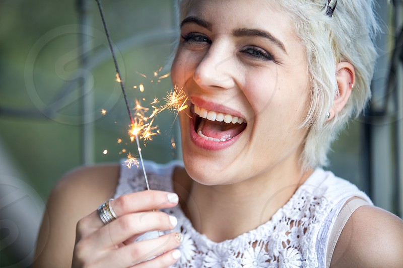 Beautiful woman laughing with a sparkler photo