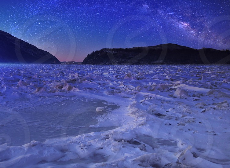 snow fields with a background of 2 mountains and blue night skies photo