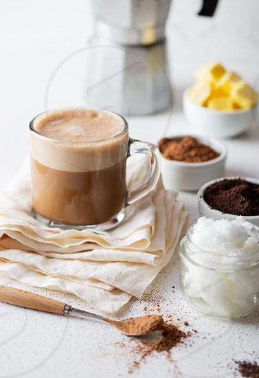 KETOGENIC KETO DIET DRINK. Coffe and cacao blended with coconut oil. Cup of bulletproof coffe with cacao and ingredients on white background. photo