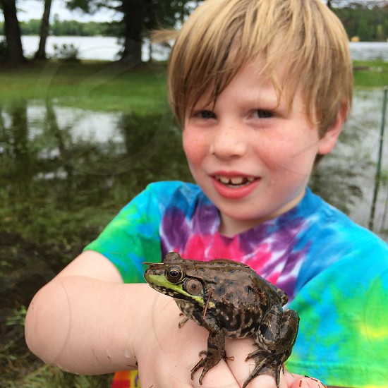 boy in blue pink and purple round neck t shirt holding a brown frog photo