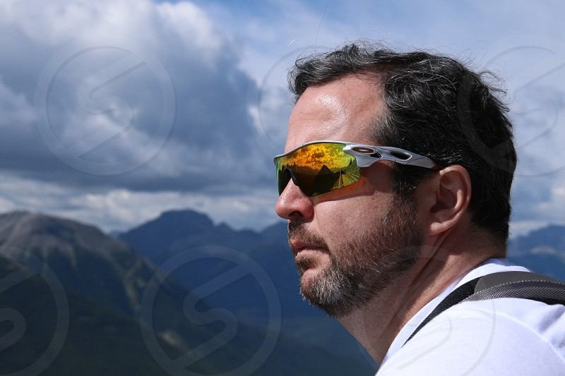 man in white shirt and sports sunglasses looking out over green mountains photo
