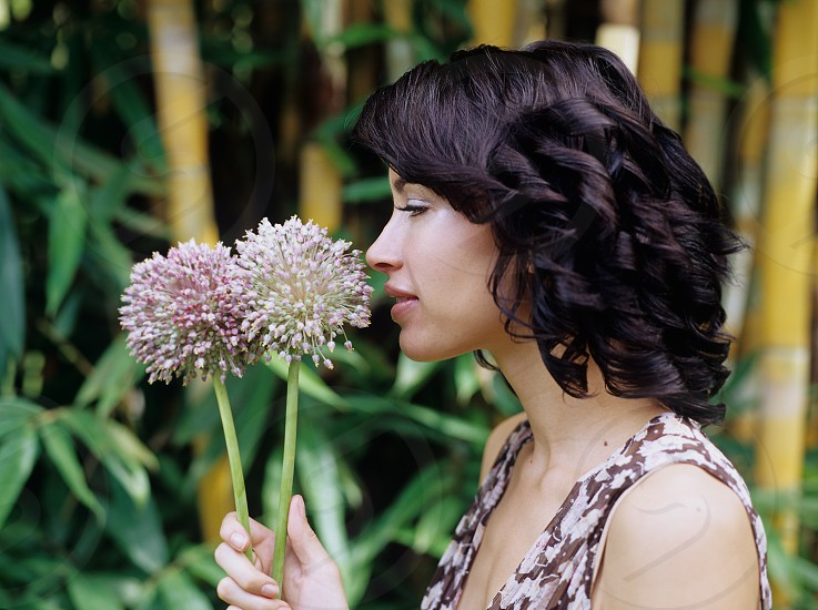 Side profile of a beautiful caucasian woman smelling flowers in a tropical setting photo