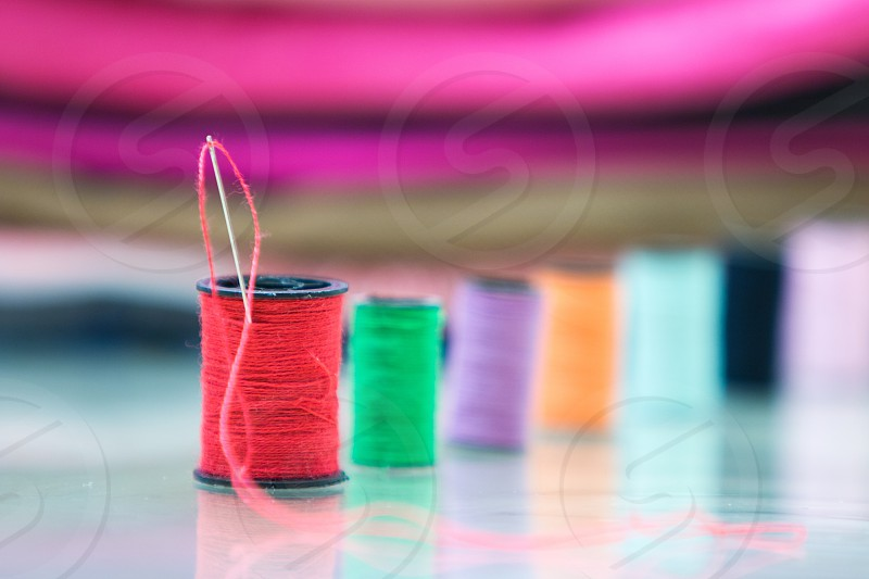 focused photography of a red thread in black spool with needle photo