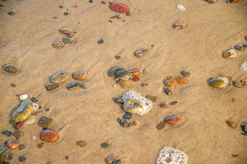 pebbles in the water of the surf photo
