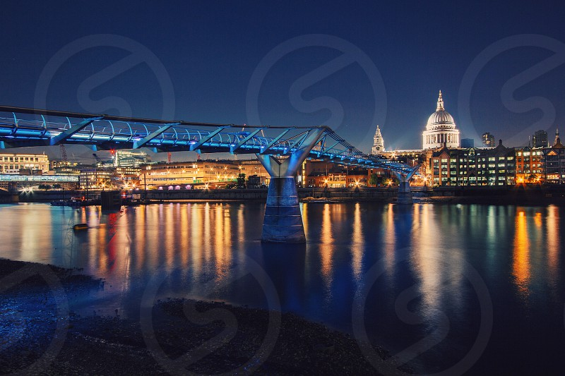 bridge across river in city at night with lights reflected in water photo