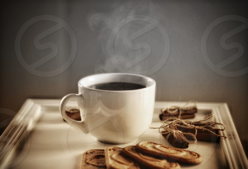 One cup of steamed drink cinnamon and biscuits perfect treat for a warm winter day during Christmas photo
