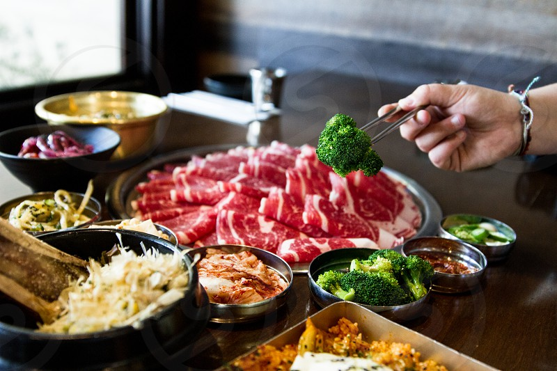 person using chopstick with broccoli near raw meat on black table photo