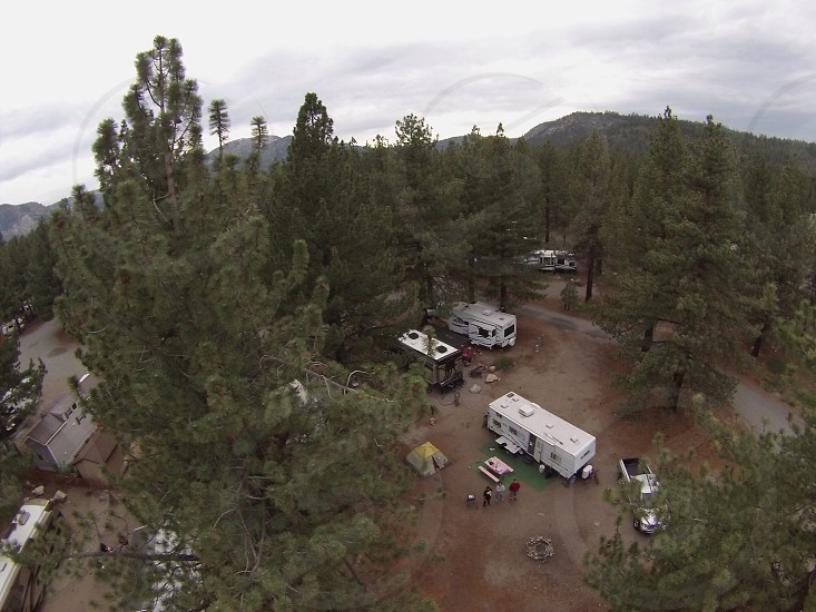 birdseye photo of white RV trailer in the forest during daytime photo