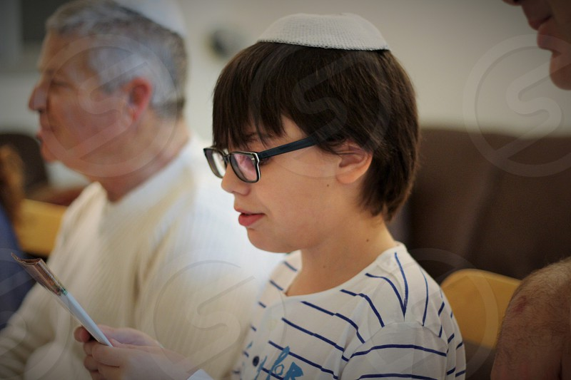 boy with black framed eyeglasses reading a music note photo