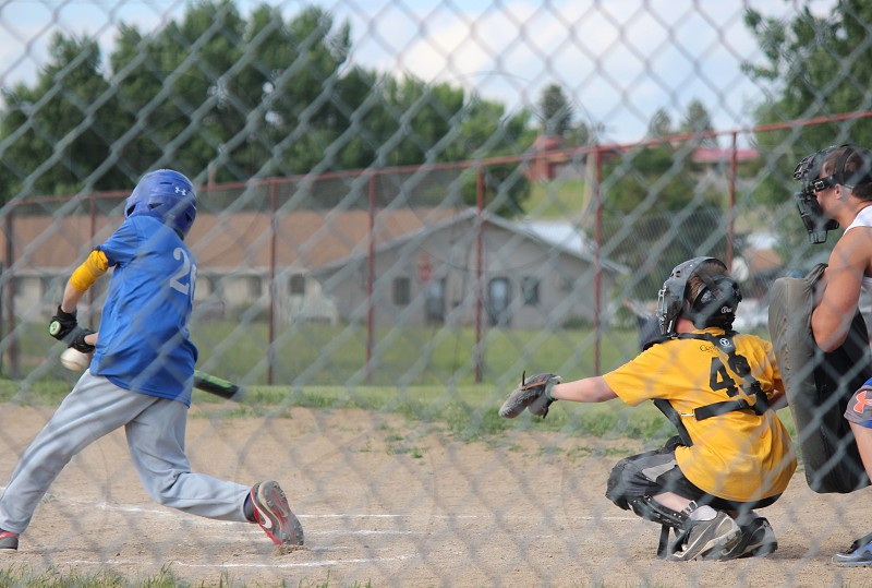 person bating a baseball with catcher behind and referee photo
