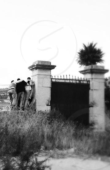 3 people standing at side on gate in grayscale photo