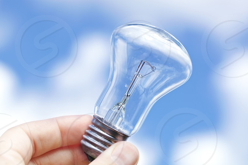 An incandescent lamp against the blue sky with clouds. photo
