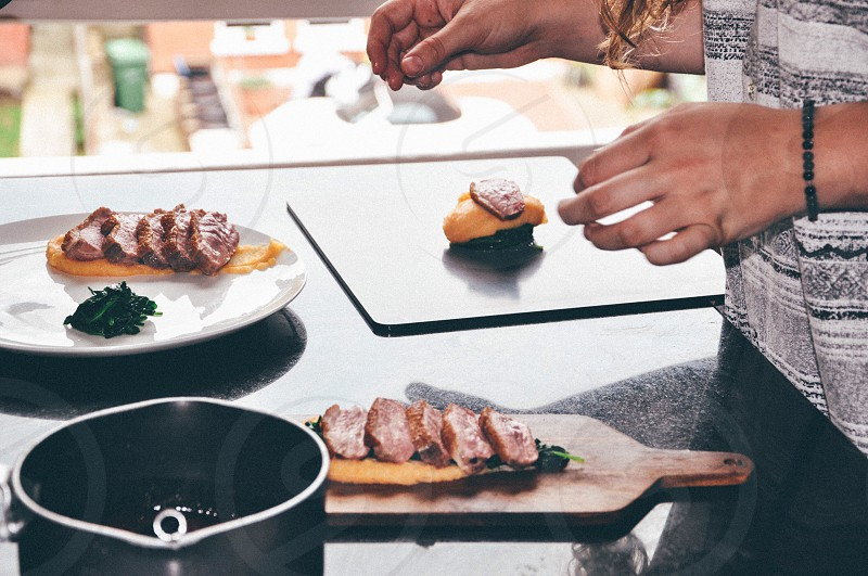 person wearing black beaded bracelet preparing omelette and rib eye sushi near white round ceramic plate with multiple rib eye cuts put on omelette strip photo