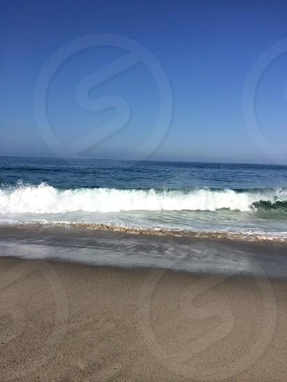 Waves break against the shore.  photo