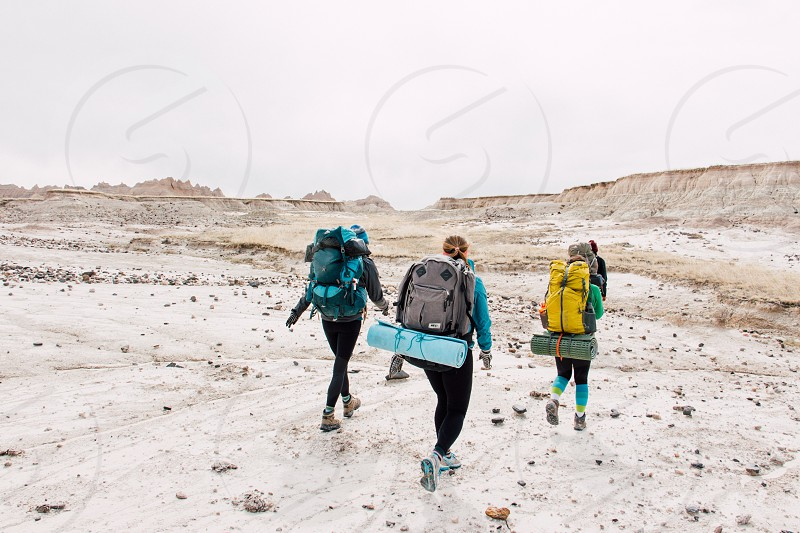 3 people carrying hiking backpack walking on brown dessert during daytime photo