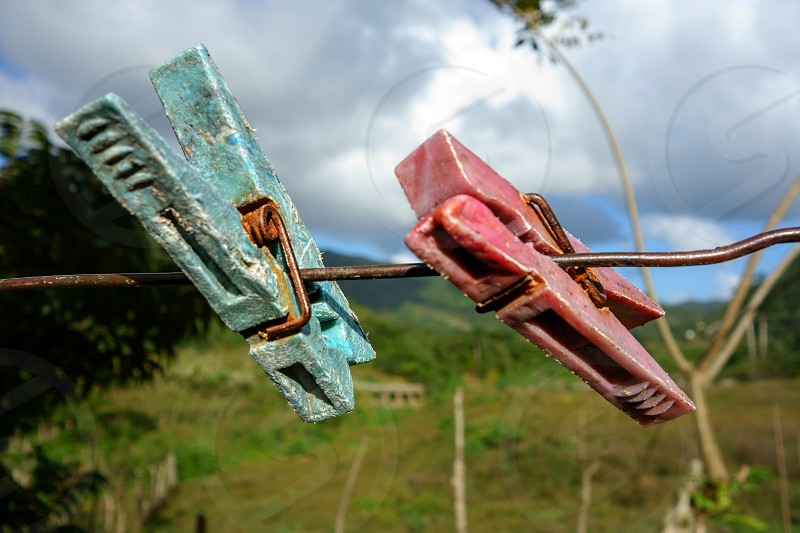 Two old and weary clothespin as friends on an outdoors clothes line in a tropical setting in Manicaragua Cuba on Christmas eve 2013. photo