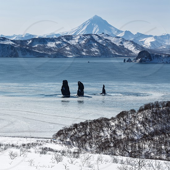 Beautiful landscape of Kamchatka: view on Three Brothers Rocks in Avachinskaya (Avacha) Bay and Viluchinsky Volcano. Far East Russia Kamchatka Peninsula. photo
