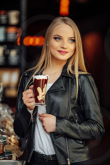 Pretty girl hold a cup of delicious coffee and waer glasses. Sun shine photo with girl drink her cappucino photo