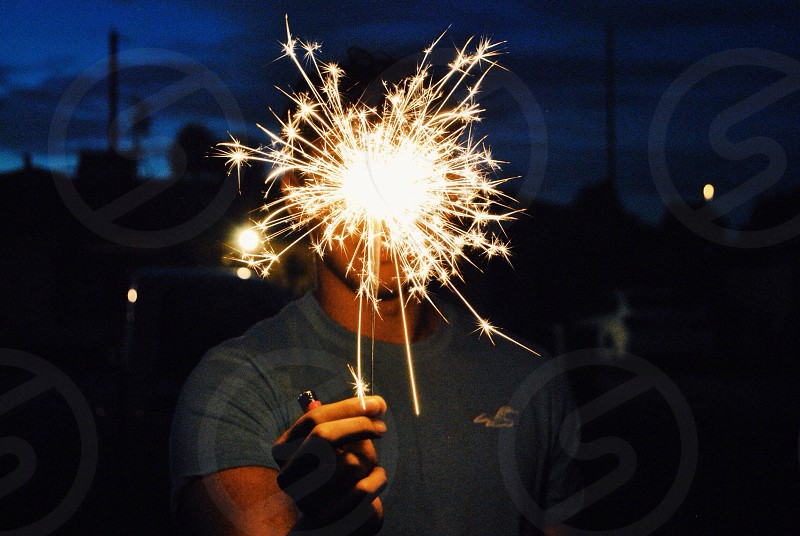man in gray hollister crew neck t shirt holding sparkler photo