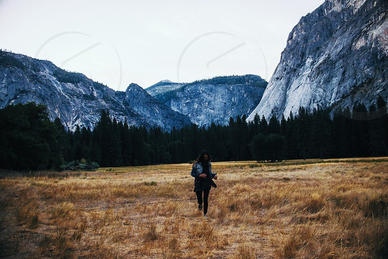 person running through yellow grass in valley photo