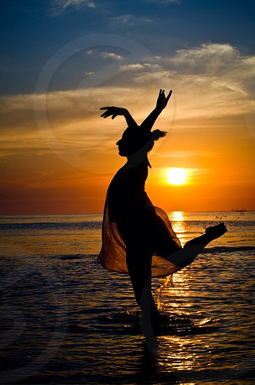 woman standing on one foot raising both hands on the water during sunset photo