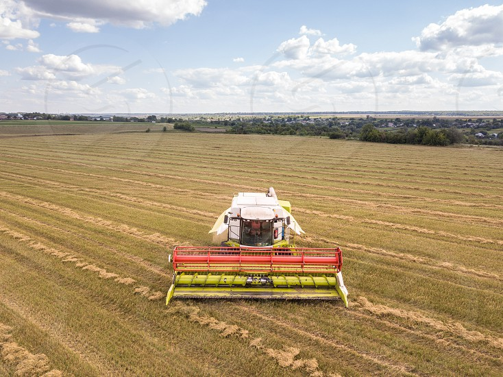 Aerial view from drone on an agricultural field with powerful combine on it on a background of blue sky in a summer time. photo