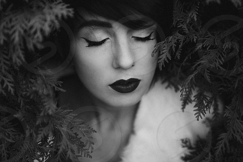 woman in make up and white fur in cedar branches  photo