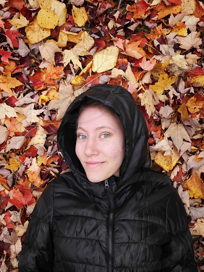Girl laying in fall leaves photo