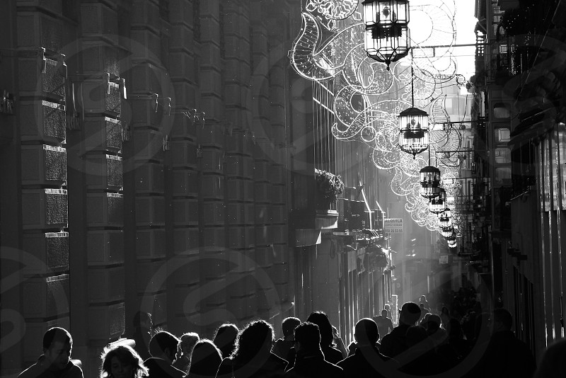 Light streams down a pedestrian shopping street in the late afternoon in Granada Spain. photo