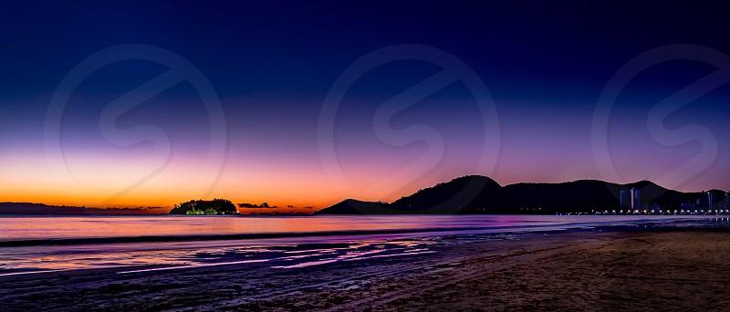beach near mountains during sun set photo