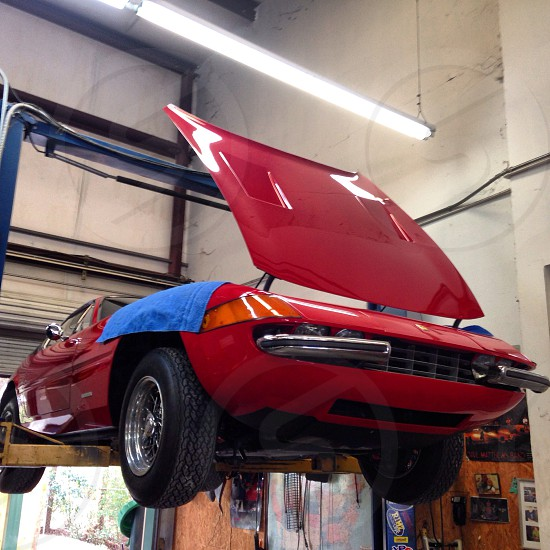 red coupe with open hood on yellow lift at garage photo