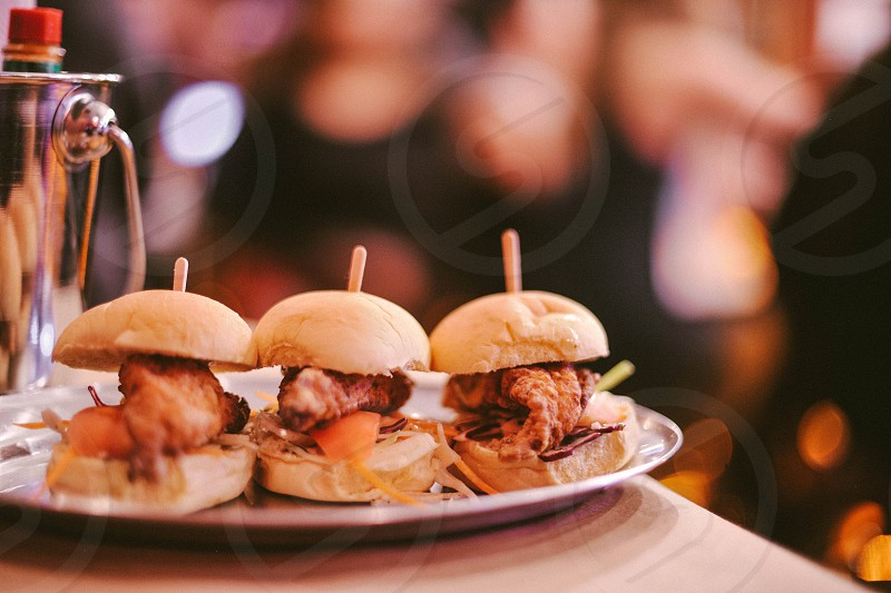 three deep fried shrimp sliders on a silver oval tray on a table photo