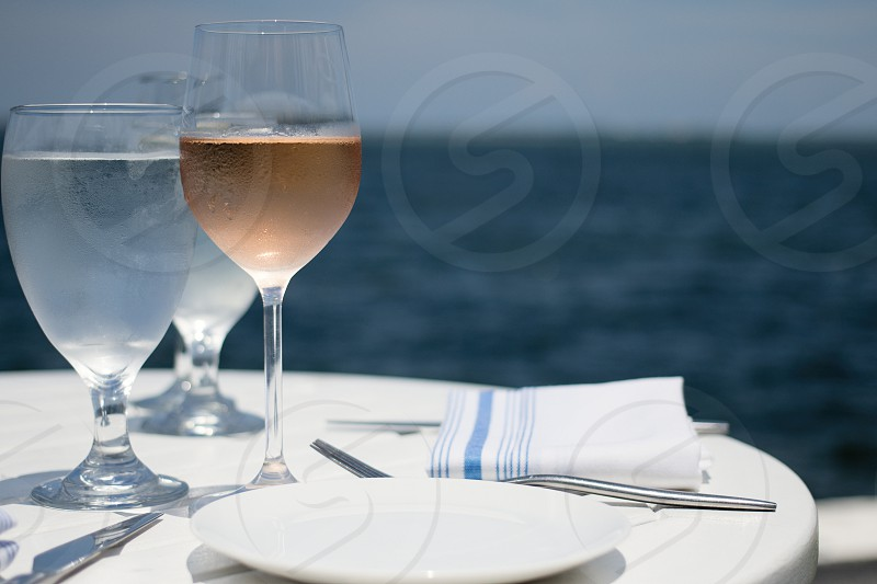 selective focus photography of half empty wine glass beside white ceramic plate photo