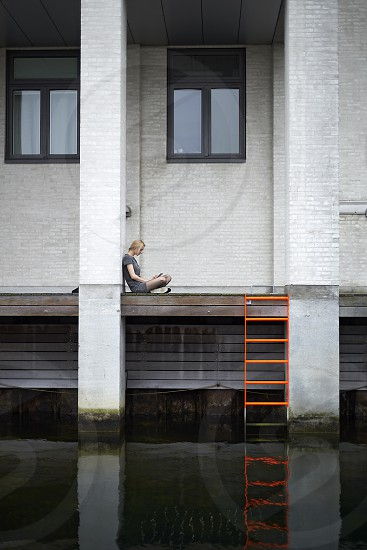 Young metropolitan woman sitting outdoors in an urban environment working on her laptop photo