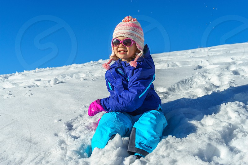 girl in blue bubble jacket and teal pants sitting on snow covered field photo