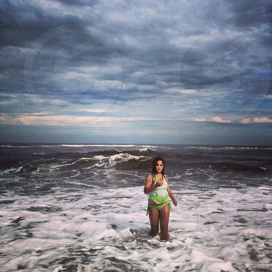 woman wearing white and green bikini swimsuit standing on seashore photo