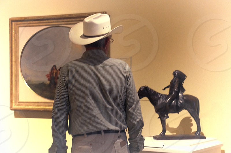 en from behind a cowboy studies a sculpture of a Native American riding a horse photo