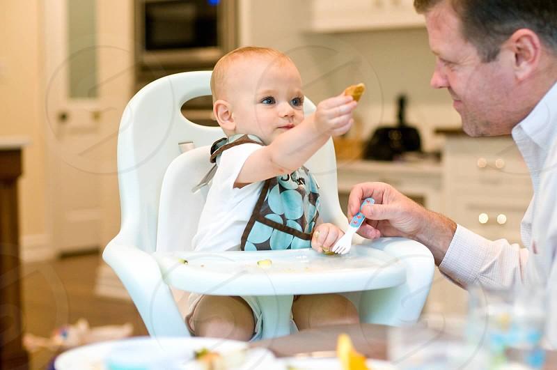 man wearing white dress shirt beside baby wearing white t-shirt sitting on high chair photo
