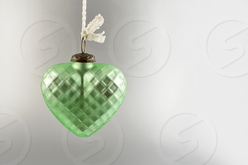 Vintage christmas decoration. Vintage christmas hanging green heart. Christmas decoration on a silver background. Holiday background with copy space for text photo