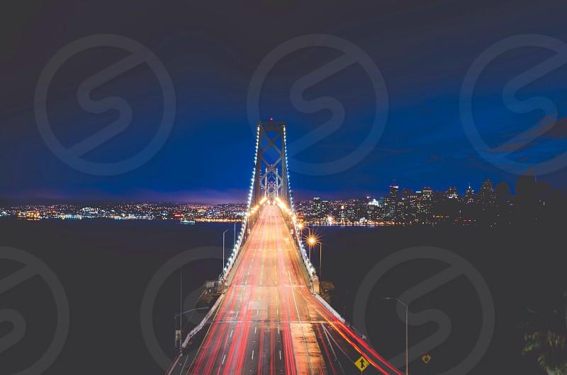lighted concrete bridge at night photo