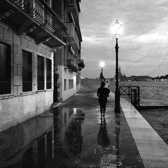 gray scale photo of woman beside body of water and high storey building photo
