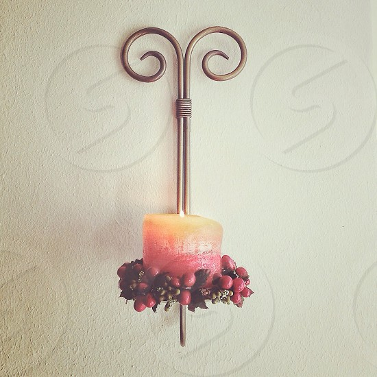 yellow red cylindrical candle in wall-mounted bronze wire candleholder photo