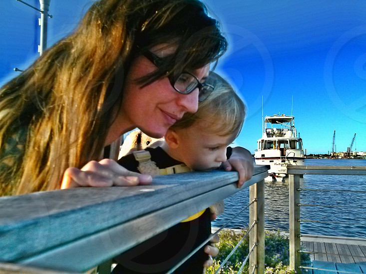 Mother and baby (toddler child boy) on dock on Intracoastal Waterway Florida with boat in the water in the background photo